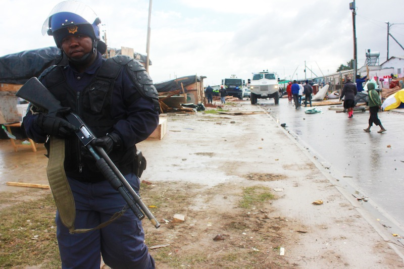 An armed police officer stands watch in Lwandle. (Ra'eesa Pather)