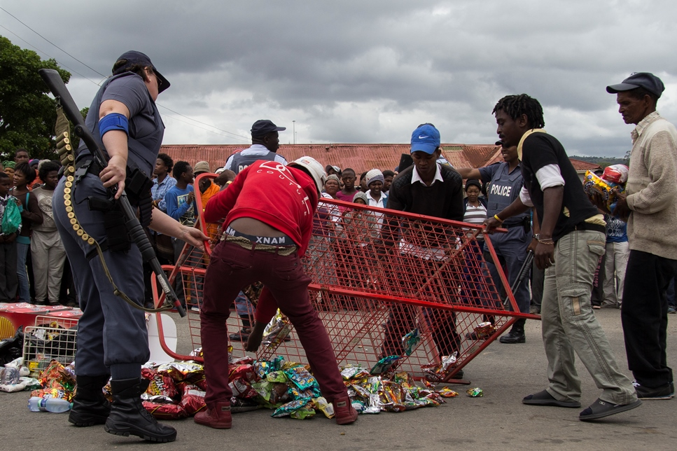 In order to avoid bloodshed the goods from a Pakistani shop are placed in the road to be dispersed amongst a crowd following an attempted break-in on Albany Road in Grahamstown on 23 October 2015. Police, security and community leaders assisted in the removal of all valuable goods before the perishables were given away. Photo: Jeff Stretton-Bell