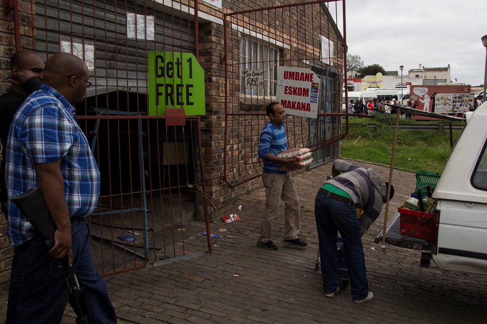 Police stand guard as shop owners clear their looted shop in Grahamstown, Eastern Cape on 22 October 2015. The town was in turmoil as residences looted shops belonging to foreign shop owners suspected for a spree of murders and corps mutilations. Photo: Jeff stretton-Bell
