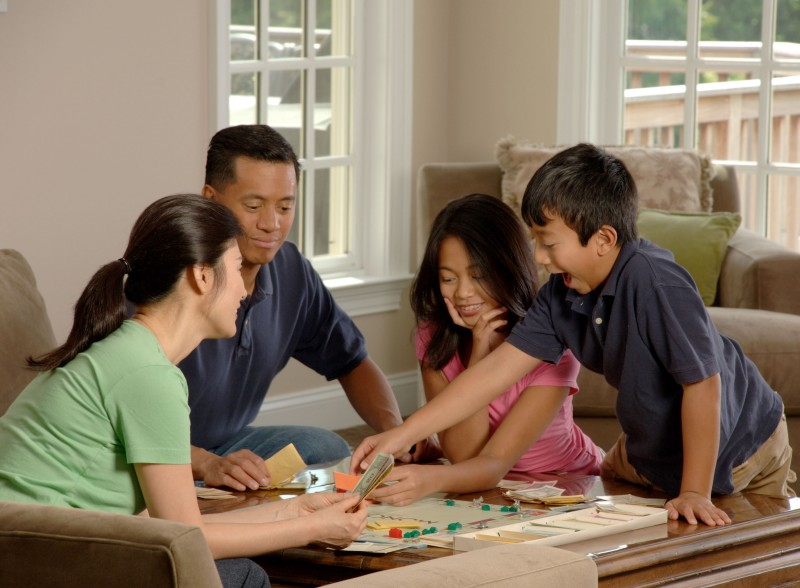 Family playing a board game [wikimedia]