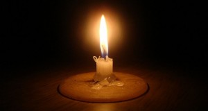 Load shedding candle in the dark [Flickr] [Wikimedia]
