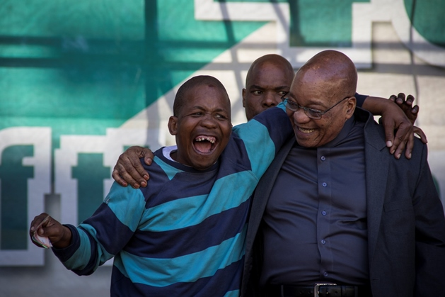 Collin Thauke (32), a regular at African National Congress (ANC) events, gets requested on stage by President Jacob Zuma after he danced and sang at the foot of the stage. Presidential security is ever vigilant as Tahuke embraces Zuma heartily.