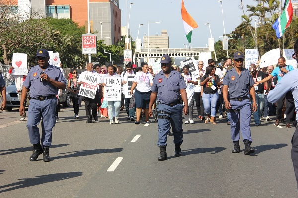 Police monitor activists marching to the Indian consulate in Durban