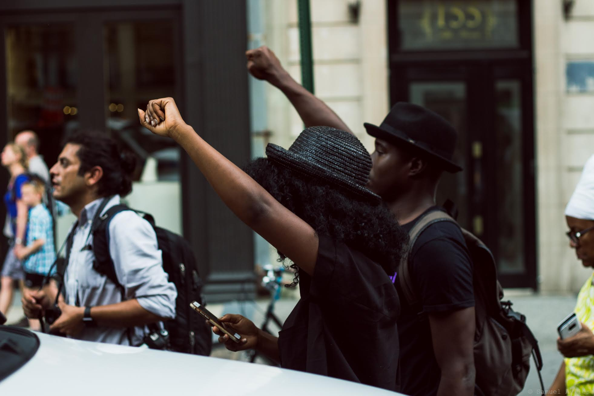 Pair marches in the street during Thursday July 7th, 2016 police brutality protests in Manhattan, New York. The protest is in response to the two recent shootings of black men by the police.