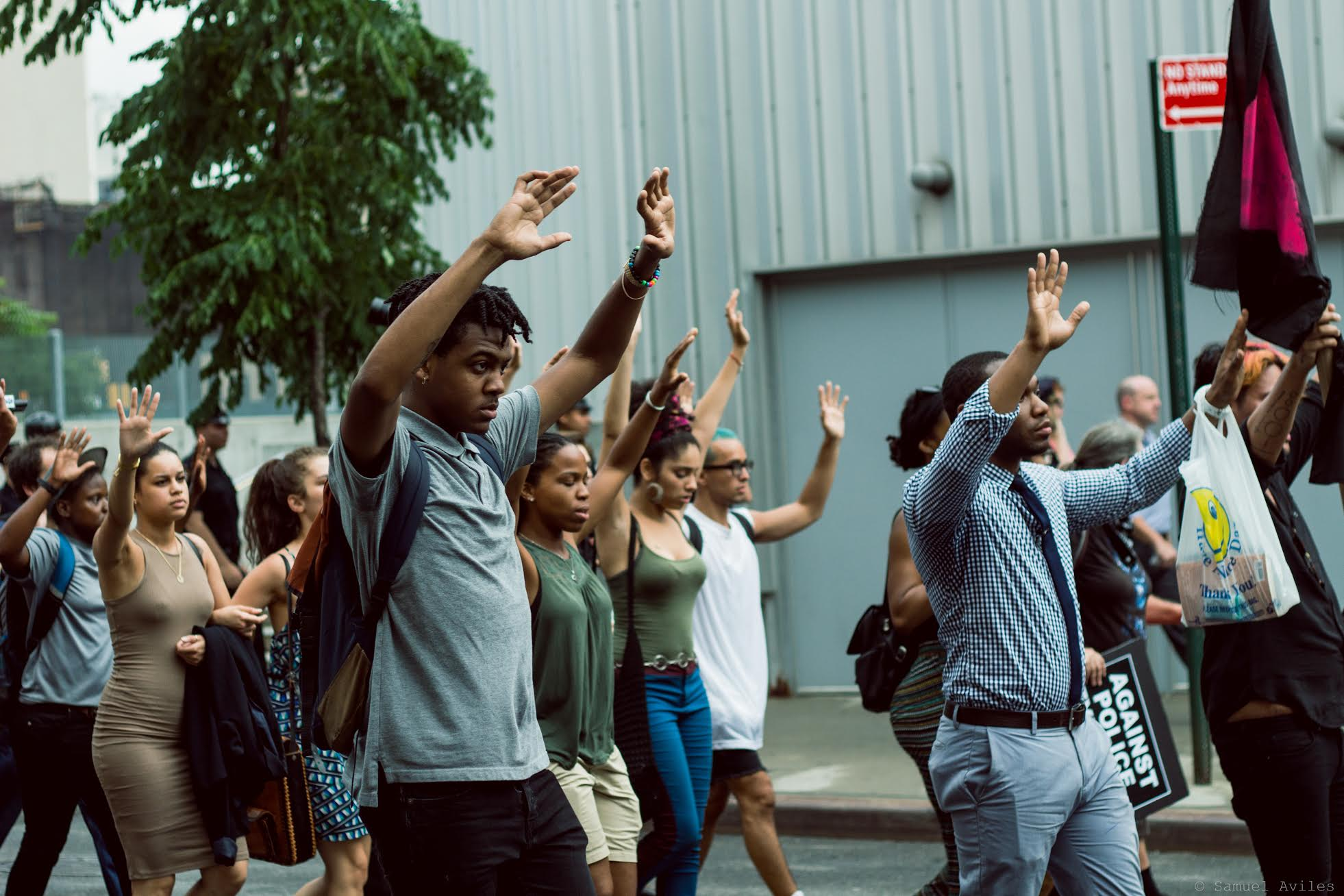 """Protestors hold up their hands during the """"hands up, don't shoot"""" chant on July 7th, in Manhattan, New York. The march went through most major areas in Manhattan."""