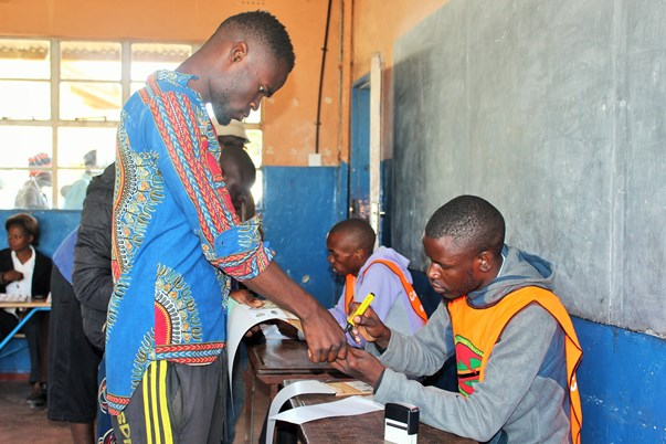 Inked and counted: A young man at Chawama Primary School has his thumb marked to indicate he has voted, but the new marking method raised concern among many voters forcing the Electoral Commission of Zambia to reassure the public the procedure was above board