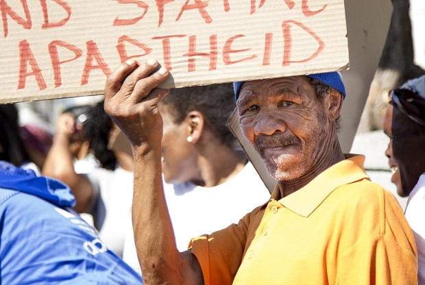 """A local resident holds up a placard during the Bromwell Street eviction protest that reads, """"Sorry for the inconvenience we're trying to end spacial apartheid"""""""
