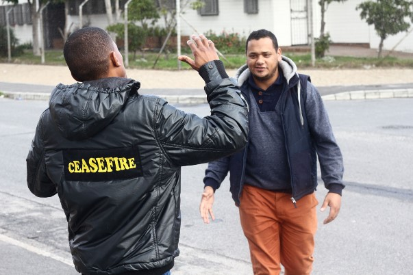 "Devon greets a Ceasefire caseworker. Both work together against gangsterism and drug abuse in Hanover Park. Devon calls Shakur a ""poet for the people."""