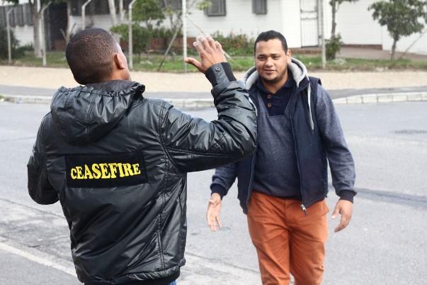 "Devon greets a Ceasefire caseworker. Both work together against gangsterism and drug abuse in Hanover Park. Devon calls Shakur a ""poet for the people."""