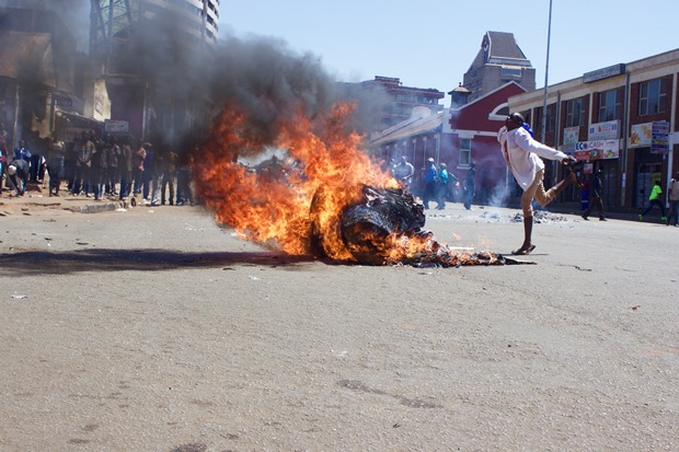 A protester dances by a fire on Jason Moyo Street, Harare.