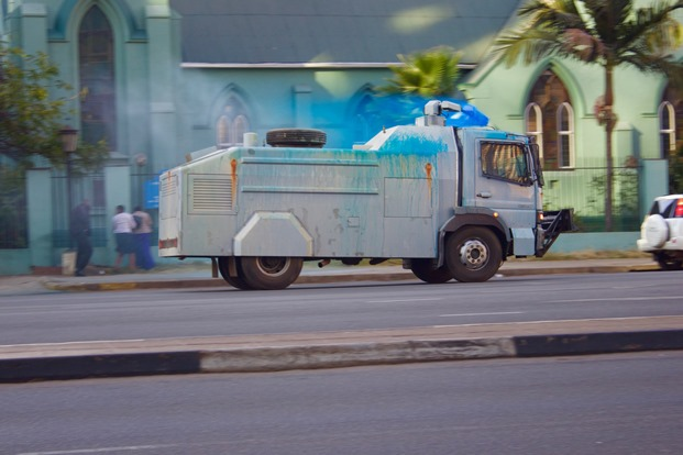 A water cannon truck squirts chemicalised water on non-protesters making their way home from work and they run for cover into a church on Samora Machel Avenue.