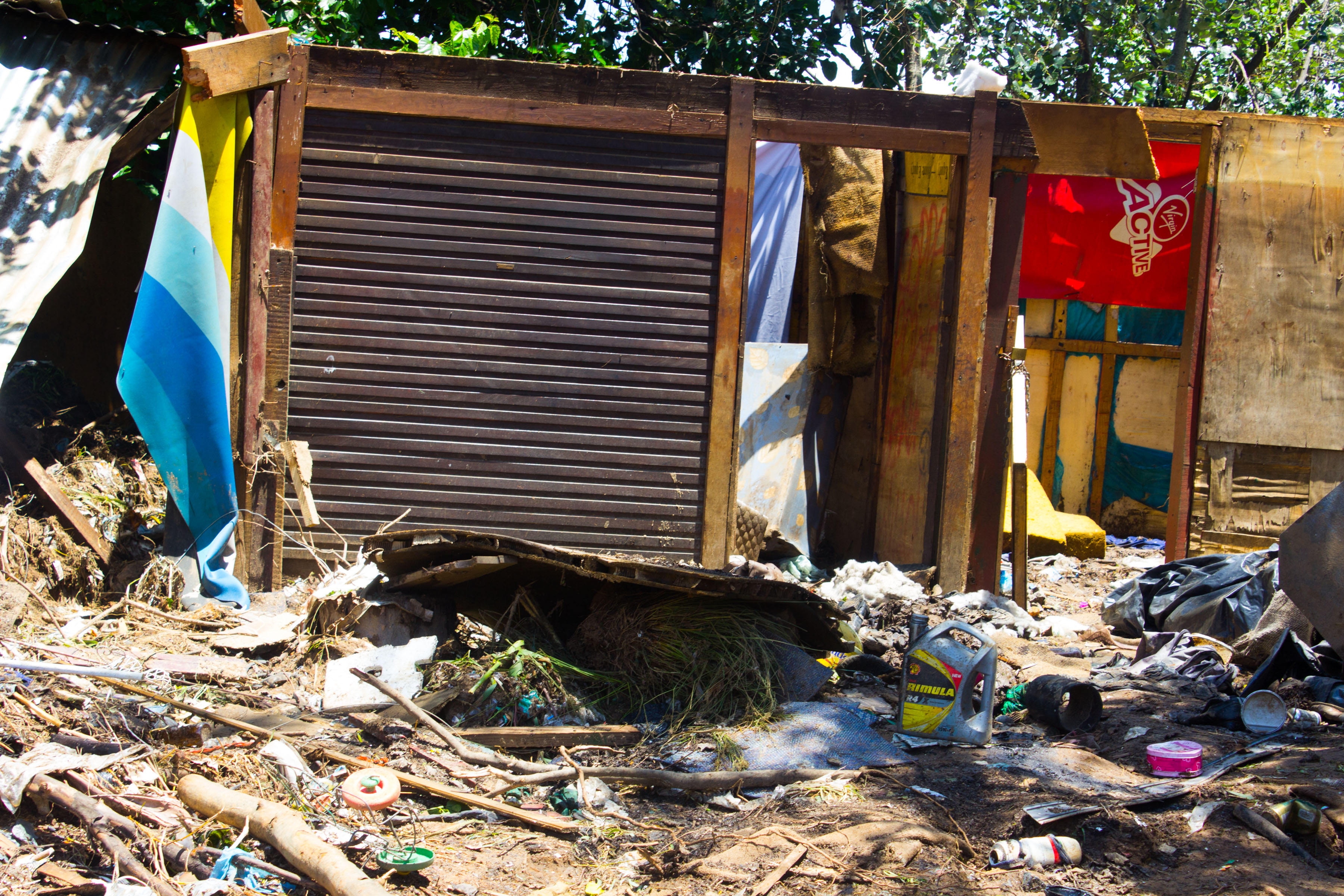 Shacks destroyed by the floods close to where at least two people were swept away by the water.