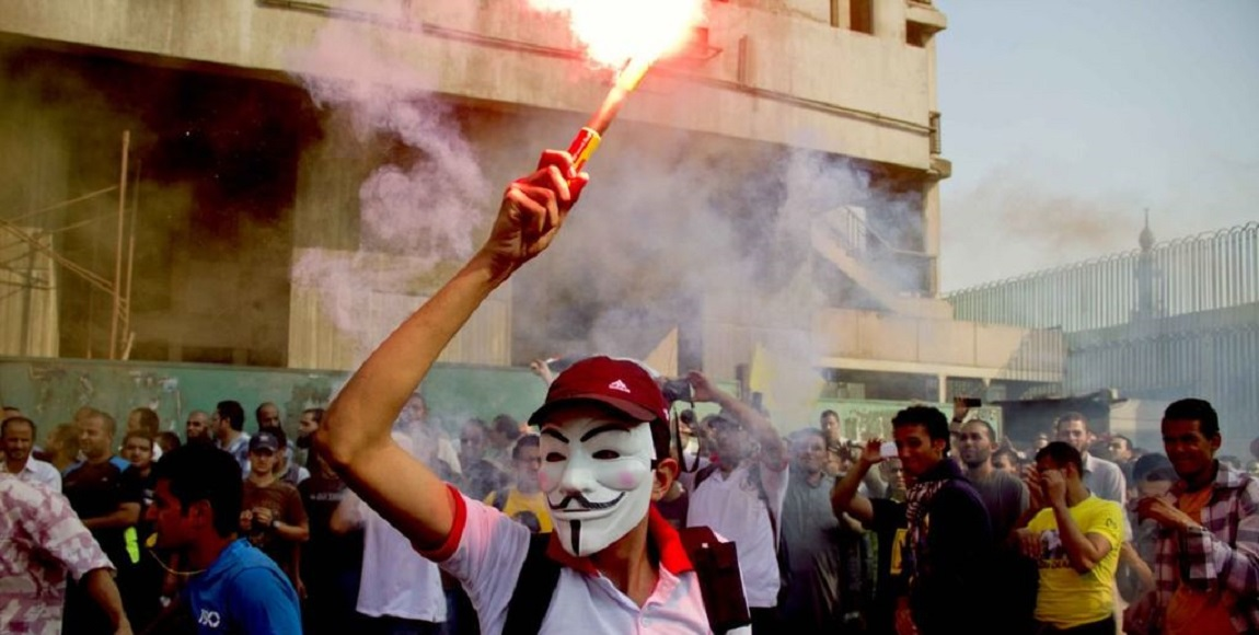 https://upload.wikimedia.org/wikipedia/commons/thumb/d/df/Anti-coup_protester_wearing_Guy_Fawkes_mask_-_demonstration_in_Cairo_6-Oct-2013.jpg/1024px-Anti-coup_protester_wearing_Guy_Fawkes_mask_-_demonstration_in_Cairo_6-Oct-2013.jpg